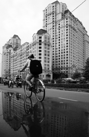 HO CHI MINH, VIET NAM- DEC 15: Young boy ride bicycle on street with high-class high-rise building background, the building reflect on surface water on street  in Ho Chi Minh, Viet Nam on Dec 20, 2013