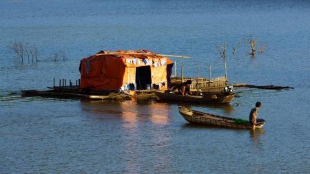 DAKLAK, VIET NAM- DEC 31:Tranquil,calm scene at evening on fishing village, small thatched house and boat tint by golden light, Daklak, Vietnam, Dec 31,2013                                         Stock Photo - 24957830