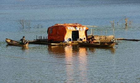 DAKLAK, VIET NAM- DEC 31:Tranquil,calm scene at evening on fishing village, small thatched house and boat tint by golden light, Daklak, Vietnam, Dec 31,2013                                         Stock Photo - 24957831