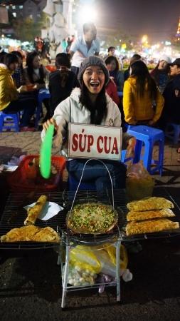 dalat: DA LAT, VIET NAM- DEC 29: Friendly, joyful, funny of Vietnamese street food vendor at night outdoor market  grill baked girdle cake- one of eating street, in Dalat, Vietnam on Dec 29,2013 Editorial