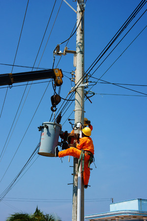 vietnamse: BINH THUAN, VIETNAM- JAN 23: Two electrician repair system of electric wire, they wear safety working clothing, climb and work on electric pole with team under blue sky, Viet Nam, Jan 23, 2014 Editorial
