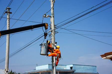 BINH THUAN, VIETNAM- JAN 23: Two electrician repair system of electric wire, they wear safety working clothing, climb and work on electric pole with team under blue sky, Viet Nam, Jan 23, 2014