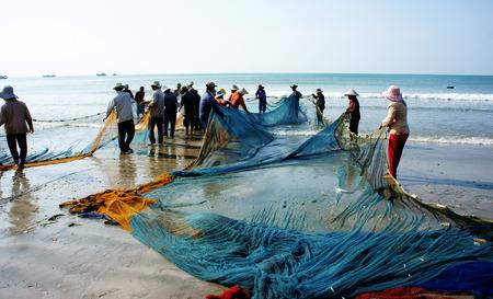ビントゥアン、ベトナム JAN 22: 印象の漁師の手で、ベトナム、2014 年 1 月 22 日長い網を持つ人々 のプル魚ネットでは、行のグループとビーチに混雑