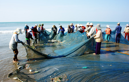 fishingnet: BINH THUAN, VIETNAM- JAN 22: Crowded atmosphere on beach with impression s group of fisherman pull fish net, row of people with long net in hand, Viet Nam, Jan 22, 2014