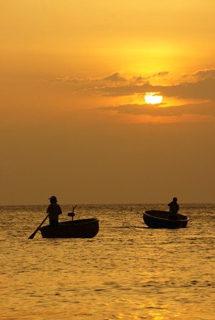 Beautiful landscape on ocean with silhouette of two fisherman standing and rowing on circle boat at sunset. photo