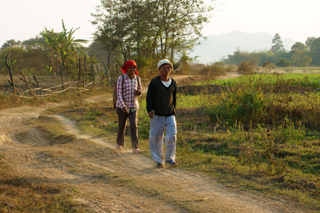 coming home: DAKLAK, VIETNAM- FEB 7: Couple of farmer walking on path at countryside to coming home, they walk on dust track in evening make calm view, Viet Nam, Feb 7, 2014