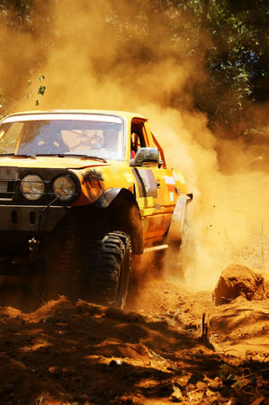 the jeep: Racer at terrain racing car competition, the car try to cross extreme off road with red earth,  wheel make splash of soil and dusty air, competitor  adventure in championship spirit  Stock Photo