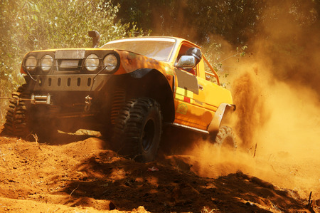 Racer at terrain racing car competition, the car try to cross extreme off road with red earth,  wheel make splash of soil and dusty air, competitor  adventure in championship spirit  Archivio Fotografico