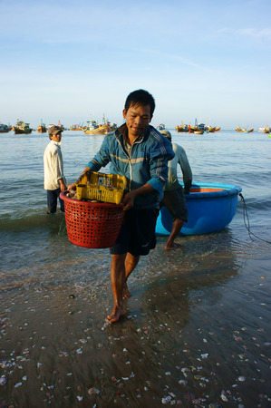 PHAN THIET- VIETNAM- JAN 21   Seafood market on beach, people trader fishing product in morning, boat on water,  person carry fresh food, Viet Nam, Jan 21, 2014 Editorial