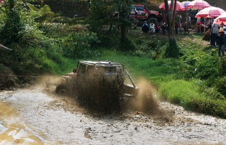 wade: DAMBRI, VIET NAM- FEB 23: Racer offroad at terrain racing car competition, motor wade cross lake, splash mud, competitor  adventure in strong spirit, audience on lakeshore, VietNam, Feb 23, 2014 Editorial