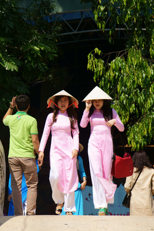 conical hat: HO CHI MINH, VIETNAM- MARCH 8: Group of young girl in Vietnamese traditional dress - conical hat, ao dai- walking in park on Aodai festival, they so charming, sweet, beautiful, Viet Nam, March 8, 2014