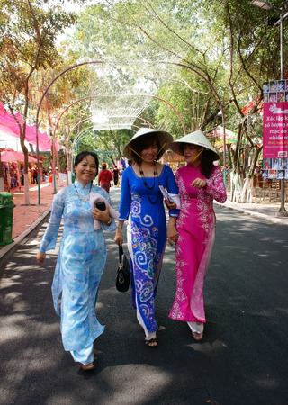 HO CHI MINH, VIETNAM- MARCH 8  Group of woman in Vietnamese traditional dress -conical hat, ao dai- with smile face, walking in park, lady so charming, sweet, happy, beautiful, Viet Nam, March 8, 2014 Editoriali