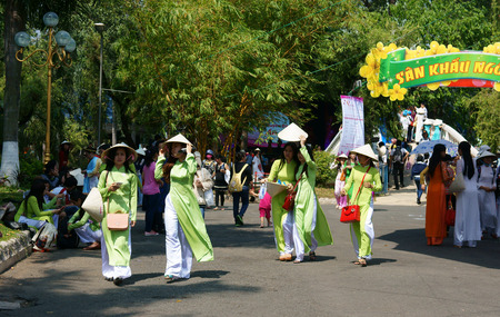 conical hat: HO CHI MINH, VIETNAM- MARCH 8  Group of young girl in Vietnamese traditional dress - conical hat, ao dai- walking in park on Aodai festival, they so charming, sweet, beautiful, Viet Nam, March 8, 2014 Editorial
