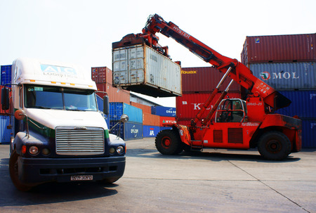 HO CHI MINH CITY, VIET NAM- MAR 19  Forklift truck crane container to trailer at freight depot, cargo box in stack, industrial port is logistic service of import, export  goods ,Vietnam, Mar 19, 2014 Editorial