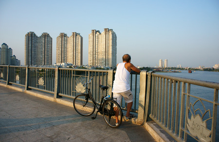 HO CHI MINH, VIET NAM- MAR 12  Healthy lifestyle of citizen at evening, ride bicycle to do exercise, stand on handrail of bridge to relaxed, enjoy a view, building at riverside, Vietnam, Mar 12, 2014