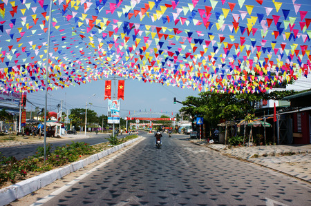 PHAN RANG, VIET NAM, JAN 24  Impression with decoration on street to celebrate holiday, people hang many string of small colorful flag, it reflect shade on surface of road, Vietnam, Jan 24, 2014