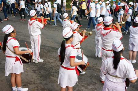 HO CHI MINH, Vietnam-06 de abril Grupo de adolescente tocar instrumentos musicales como el tambor, clarinete, con uniforme blanco, forraje-casquillo, lazo rojo, la bandera roja que llevan a cabo en el evento social, Vietnam, 06 de abril 2014