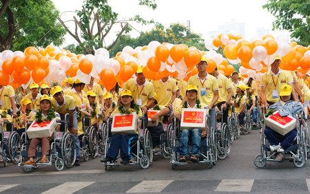 philanthropist: HO CHI MINH, VIET NAM- APRIL 6  Group of invalid people sitting on wheelchair in a row with young volunteer on street, begin charitable activity event for handicapped community, Vietnam, April 6, 2014