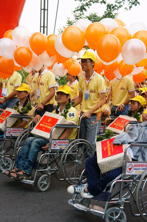 air bladder: HO CHI MINH, VIET NAM- APRIL 6  Group of invalid people on wheelchair in a row with young volunteer on street, begin charitable activity event for handicapped community, Vietnam, April 6, 2014 Editorial