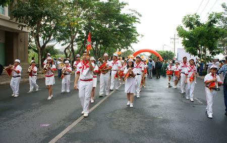 zampona: HO CHI MINH, Vietnam-06 de abril de equipo de adolescente tocando instrumentos musicales como el tambor, clarinete, con uniforme blanco, forraje-casquillo, lazo rojo, la bandera roja que camina en el evento social, Vietnam, 06 de abril 2014