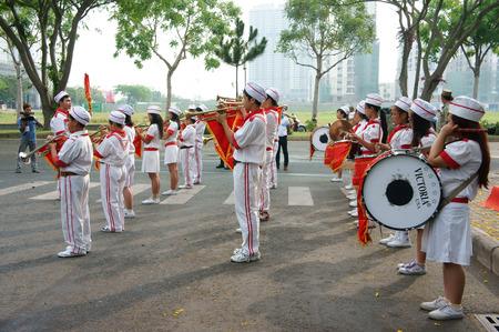 zampona: HO CHI MINH, Vietnam-06 de abril de equipo de adolescente tocar instrumentos musicales como el tambor, clarinete, con uniforme blanco, forraje-casquillo, lazo rojo, la bandera roja que llevan a cabo en el evento social, Vietnam, 06 de abril 2014 Editorial