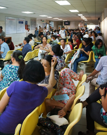HO CHI MINH CITY, VIET NAM- APRIL 4  Crowd of people sitting and waiting to examine health, sick patient sit on bench at public hospital, Saigon, Vietnam, April 4, 2014