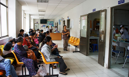 public hospital: HO CHI MINH CITY, VIET NAM- APRIL 4  Crowd of people sitting and waiting to examine health, sick patient sit on bench at public hospital, Saigon, Vietnam, April 4, 2014 Editorial