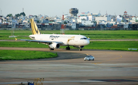 boing: HO CHI MINH CITY, VIET NAM- MAY 6  Airplane at Tan Son Nhat airport to transport, Tiger plane prepare take off, moving on runway with navigator of car , Vietnam, May 7, 2014