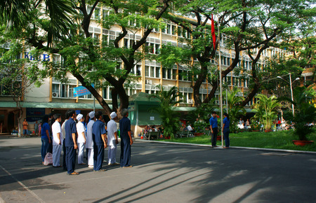 HO CHI MINH CITY, VIETNAM- MAY 19  Group of doctor and nurse standing with solemn spirit, toward flagpole, trooping the colour, sing natinal anthem in hospital yard, Saigon, Viet Nam, May 19, 2014