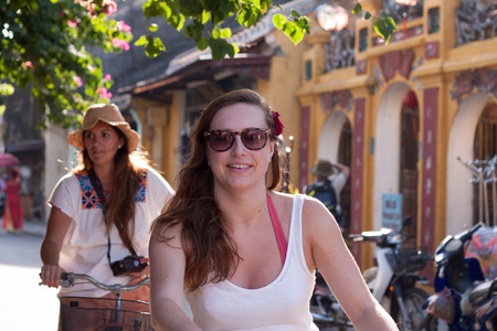 causasian:  HOI AN, VIETNAM- MAY 13  Tourist visit ancient street by riding bike, beautiful causasian woman wear glassese, smiling, happy, enjoy make tour in sunny day, Hoian, Viet Nam, May 15, 2012