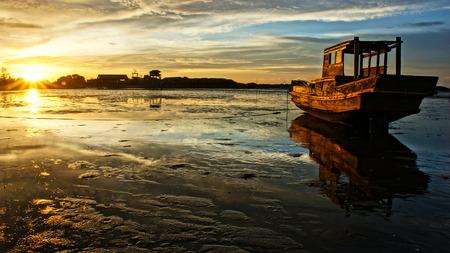going out: Paesaggio astratto di mare, quando il tramonto, marea di uscire, il sole andare gi�, splendere raggio di sole sulla barca da pesca in legno che riflettono sulle acque di superficie di spiaggia, cielo colorato in scena di sera Archivio Fotografico