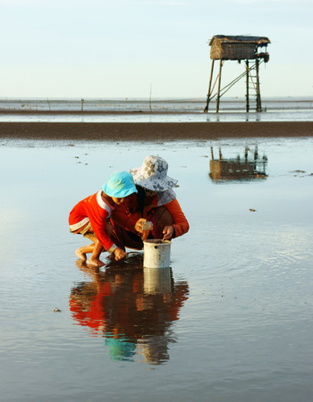 MEKONG DELTA, VIETNAM- JULY 8  Unidentified Vietnamese children, mother reflect on surface water of black sand sea, they earn money by catch shell fish before leaf watch tower , Viet Nam, July 8, 2014