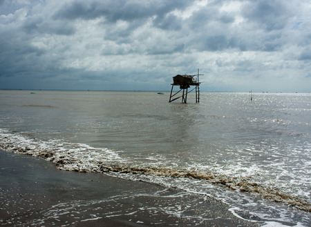 Wooden watch tower on Viet Nam beach at Mekong Delta, tower reflect on water, sea with black sand on day photo