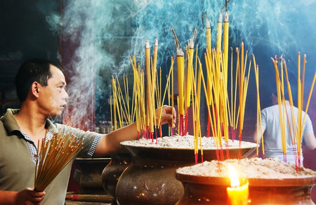 HO CHI MINH CITY, VIETNAM- AUG 10   People burn incense at ancient pagoda, incense stick in censer, smoke spriral, this traditional culture of buddhism religion, man in solemn, Vietnam, Aug 10, 2014 Editorial