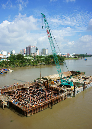 HO CHI MINH, VIETNAM- AUG 9  Construction site on Saigon river for Ben Thanh, Suoi Tien metro plan, worker work on framework, boat on canal, development of traffic infrastructure, Vietnam, Aug 9, 2014