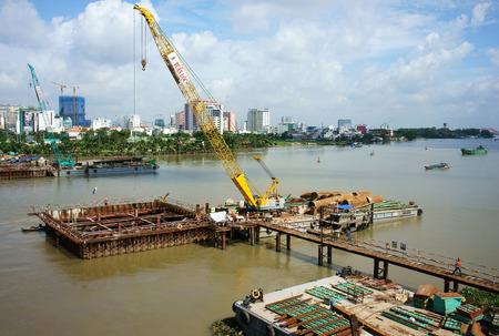 modernize: HO CHI MINH, VIETNAM- AUG 9  Construction site on Saigon river for Ben Thanh, Suoi Tien metro plan, worker work on framework, boat on canal, development of traffic infrastructure, Vietnam, Aug 9, 2014