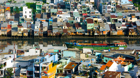 HO CHI MINH, VIETNAM-  AUG 8 Amazing landscape of  overloaded city, group of house is close, riverside home in danger, unsafe space,  city with old plan, boat on canal, Viet Nam,  August 10, 2014 Editorial