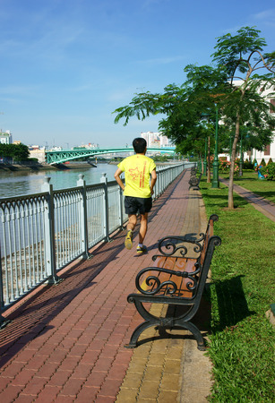 HO CHI MINH, VIETNAM-  AUG 10  People take physical exercise on the riverside park, young man jogging along Saigon river, fresh air in morning, healthy lifestyle for health, Viet Nam,  August 10, 2014