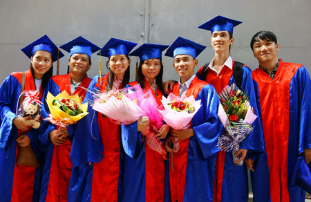 HO CHI MINH CITY, VIETNAM- AUG 8   Group of young student in gown uniform standing, hold bouquet, smile on graduate ceremony at university, young girl happy with bright future, Viet Nam,  Aug 5, 2014