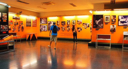 consequence: HO CHI MINH , VIETNAM- AUG 12   Tourist visit Vietnam War Remnant Museum, people looking photo of agent orange victim, consequence of war, exhibition room in orange color, Vietnam, Aug 12, 2014