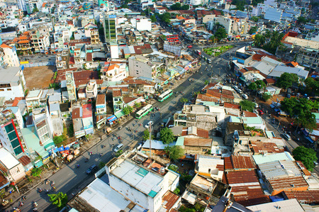 HO CHI MINH, VIETNAM- AUG 14: Amazing view of Asia city, group of private house from dense residence, vehicle move on street, urbanization urban, make increase greenhouse effect, Vietnam, Aug 14, 2014
