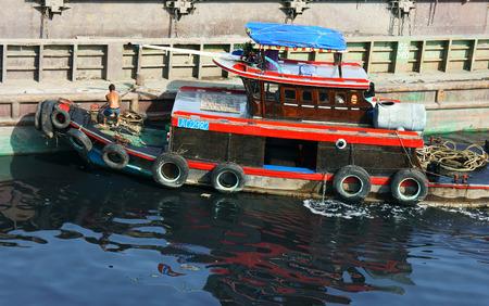 global problem: HO CHI MINH CITY, VIETNAM- 18 de agosto: Hombre vietnamita anclaje barco de madera roja, de pie en el barco, tire de la cuerda, r�o en el color negro por el agua contaminada, problema mundial de medio ambiente, Vietnam, 18 de agosto 2014
