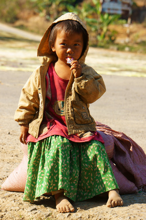 BUON ME THUOT, VIET NAM- FEB 7:Unidentified Asian children sitting on pavement, Vietnamese kid hungry and eating, dirty clothing, barefoot, poverty child at poor countryside, Vietnam, Feb 7, 2014