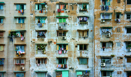 HO CHI MINH CITY, VIET NAM- SEPT 11: Impression scene of cement wall from old apartment building, group of aged window, air conditioner, block downgrade make unsafe, danger, Vietnam, Sept 11, 2014