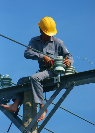 DONG THAP, VIET NAM- SEPT 23:  Asian electrician climb high in pole to work, lineman with cable network, man repair electric post danger and unsafe, is industry service, Vietnam, Sept 23, 2014