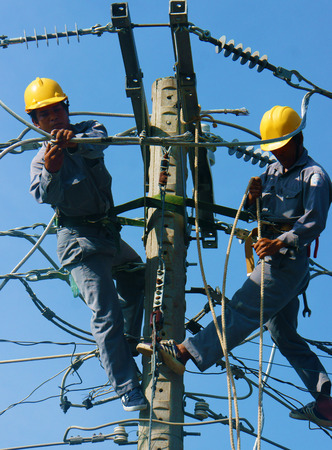 DONG THAP, VIET NAM- SEPT 23: Two Asian electrician climb high in pole to work, lineman with cable network, man repair electric post with belt safety, this is industry service, Vietnam, Sept 23, 2014