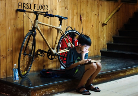 HO CHI MINH CITY, VIET NAM- OCT 12: Unidentified Asian children sitting at staircase of house with tablet, Vietnamese kid looking with high concentration, modern technology, Vietnam, Oct 12, 2014 新聞圖片