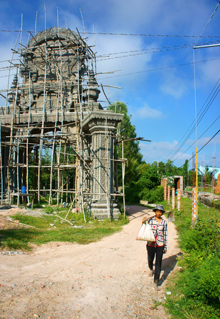 AN GIANG, VIET NAM- SEPT 20: Asian farmer carry tool walking on countryside path, construction work to construct khmer pagoda gate with pattern, development of religion, Vietnam, Sept 20, 2014