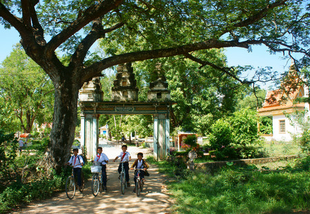 AN GIANG, VIET NAM- SEPT 20: Group of Asian primary pupil riding bike to Khmer village gate, ancient gate with large green tree, big brach make shade, kid happy with friendship, Vietnam, Sept 20, 2014