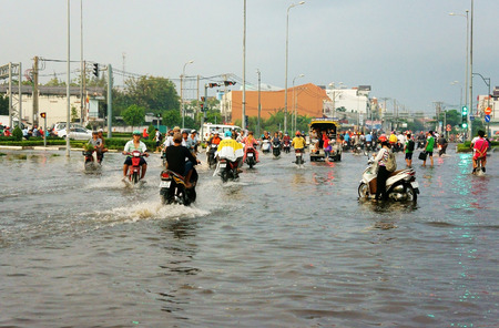 unsafe: HO CHI MINH CITY, VIET NAM- OCT 9: Hard to circulate situation at Ho Chi Minh city when flood tide, flooded water on street, vehicle traffic in water, danger, unsafe scene, Vietnam, Oct 9, 2014